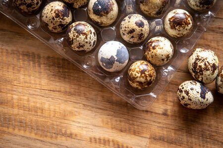 Quail eggs in  packaging on wooden background space for text Stock fotó