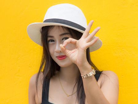 concede: Thailand women, yellow backdrop. Okay thumbs