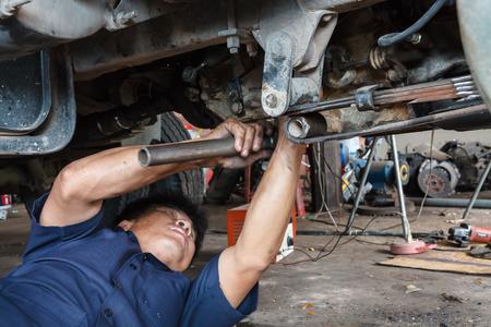 carretilla de mano: Mecánico de automóviles profesional que trabaja en el servicio de reparación de automóviles.