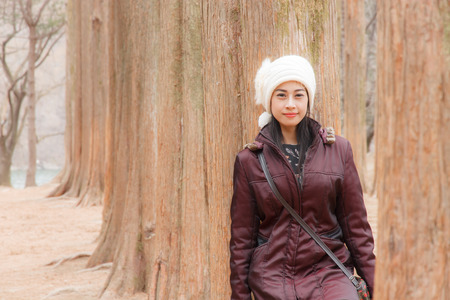 Beautiful woman leaning against a tree forest.