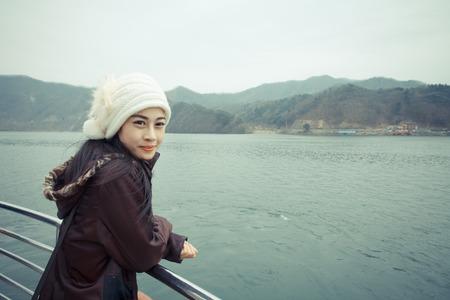 Woman wearing a jacket, standing by the river. Reklamní fotografie