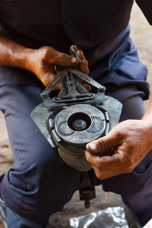 journeyman: automotive mechanic disassembling car engine with during automobile maintenance at repair service station Stock Photo