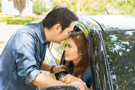 Young couple kissing on the car