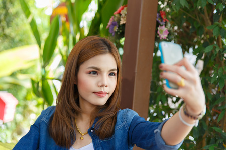Portrait of a beautiful young woman selfie in the park with a smartphone Reklamní fotografie