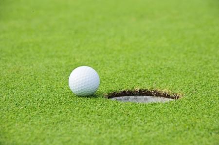 Golf Ball on Edge of Hole  Stock Photo
