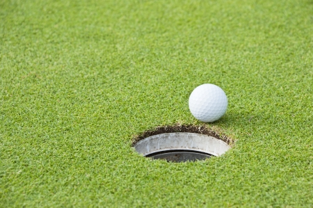 Golf Ball on Edge of Hole  photo