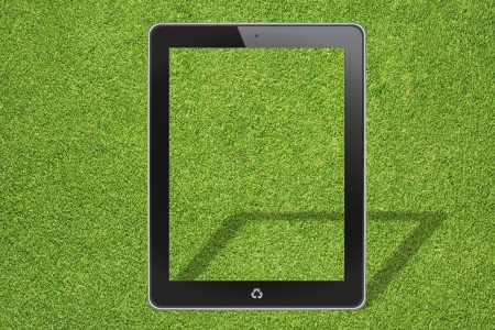 Tablet computer on green grass background photo