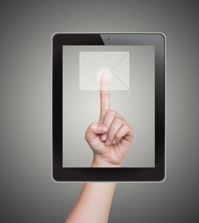 Hand pushing mail button of tablet on a touch screen photo
