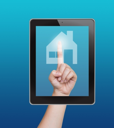 Hand pushing home button of tablet on a touch screen Stock Photo