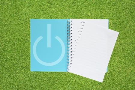 shutdown: Book with shutdown icon on grass background