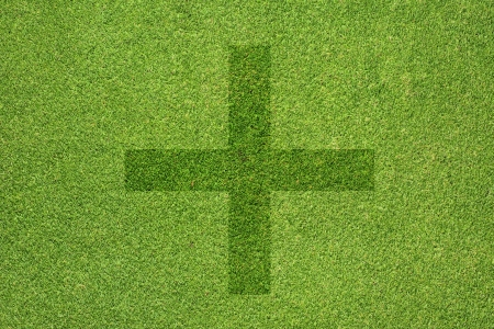 Plus icon on green grass texture and  background photo