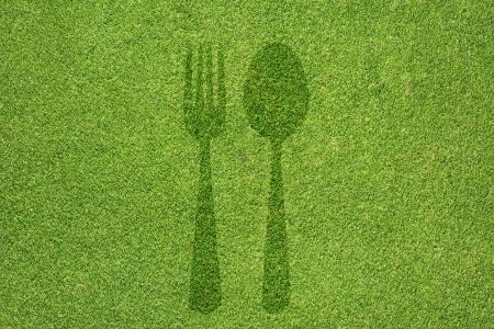 Fork and spoon icon on green grass texture and  background photo