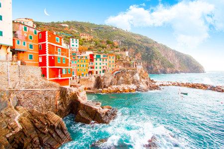 Riomaggiore on the mountain in cinque terre near mediterranean sea in Liguria - Italy and moon cloudy sky, traditional italian architecture