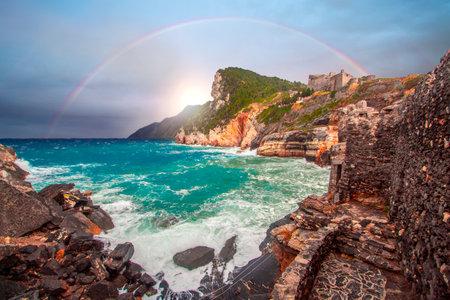 Rainbow on Portovenere (porto venere) Doria castle in Liguria Italy near cinque terre. Waves breaking on rocky coastline