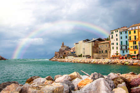 Rainbow on Portovenere (Porto Venere) in Liguria, Italy: scenic view of the Church of St. Peter (Chiesa di San Pietro) at sunset with colorful sunset nearby Cinque Terre