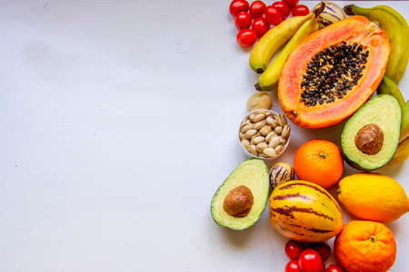 Healthy food clean eating selection: orange yellow fruit, vegetable, seeds, superfood, avocado, papaya on white concrete background