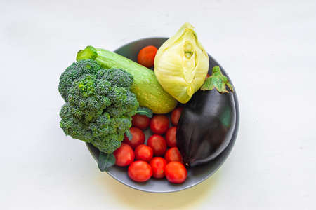 Healthy food clean eating selection: fruit, vegetable, superfood, avocado, papaya leaf vegetable in a dish on white concrete background