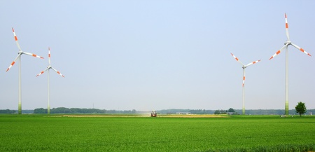 power windmills in the field and a tractor in the middle Stock Photo - 9440258