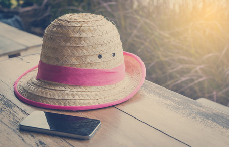 hi hat: Farmer Hat with smart phone for Modern hi technology farmer on table vintage tone. Stock Photo
