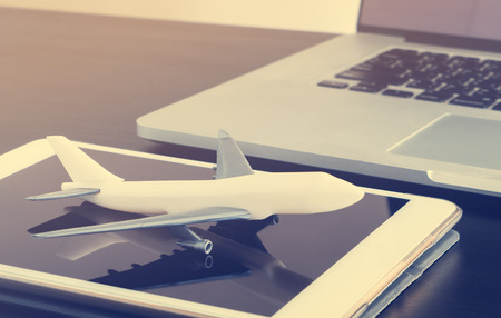 Air travel booking plane ticket on tablet internet and notebook.