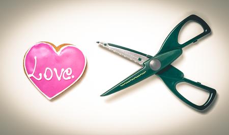sullen: Scissors cutting a heart vintage sullen background. Heart breaking. Stock Photo