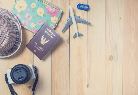 Air and land Traveller equipments flat lay on wooden background.