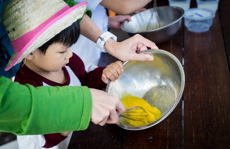 mother helping baby: Baby boy is a cooking class. Children are taking Bakery lesson. Mother helping her child preparing pastry. Stock Photo