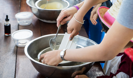 Children hand making home made ice cream cooking class. Spinning steel bowl for making Vanilla Ice Cream.