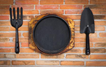 steel pan: Black Steel Pan and utensils on red brick background.