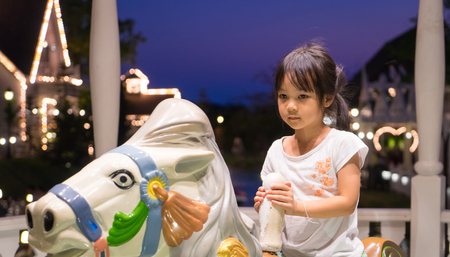 merry go round: Unhappy Asian girl riding on a house merry go round. Stock Photo