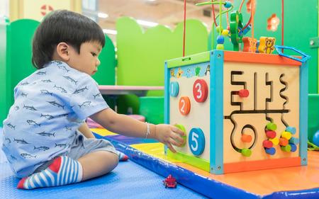 Bebé asiático que juega con el juguete educativo Foto de archivo