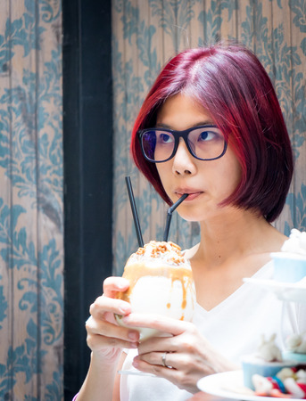 chocolate shake: Red hair asian nerdy girl having chocolate shake and macaronsin vintage cafe Stock Photo
