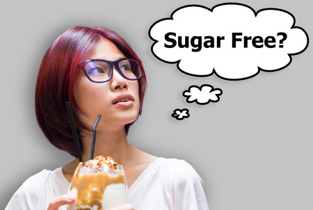 free thinking: Japanese girl thinking if her drink is sugar free or not Stock Photo