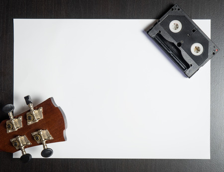 screenplay: Guitar Head with Video Tape on white paper with space.