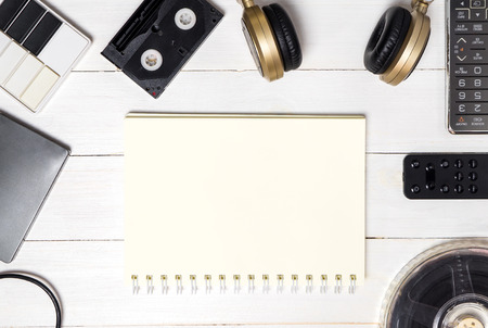 note book: Note book surrounding by technology entertainment devices. Stock Photo