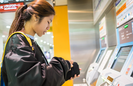 buying time: Fukuoka, Japan - March 20, 2016: Fukuoka on March 20, 2016. Tourist having a hard time buying Japan Subway ticket.