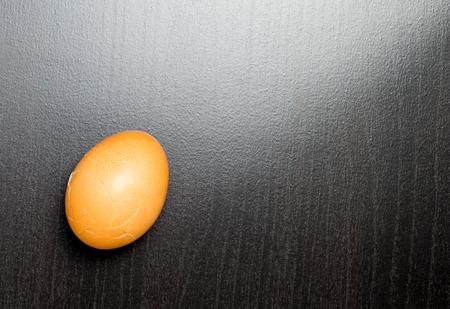 shiny black: Cracking egg on a black shiny background Stock Photo