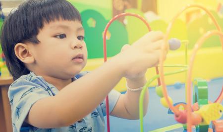 Aziatische kinderen spelen op educatief speelgoed. Japanse baby leren tellen met kleurrijke speelgoed. Nummer leren praktijk in kleuterklas ruimte voor de kinderen. Stockfoto
