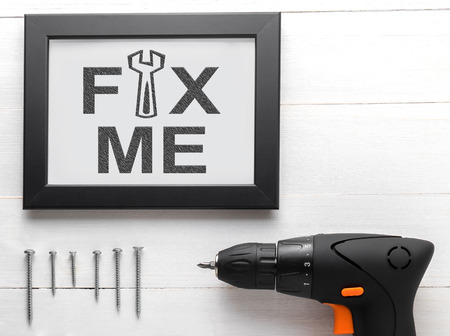 depress: Fix me text on black frame with equipments. Fix me conceptual for broken heart person or depress person asking someone to fix the person. Power drill with screws