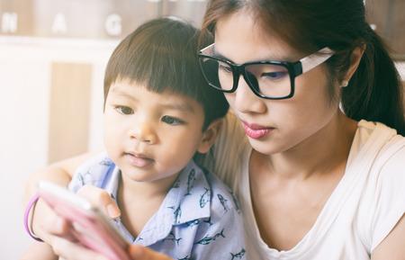 educadores: Madre que enseña a su hijo a usar el teléfono inteligente.