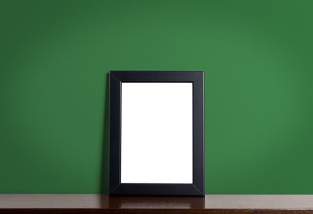 room accents: Black modern picture frame on green background. Black photo frame made of paper on a green cement texture.