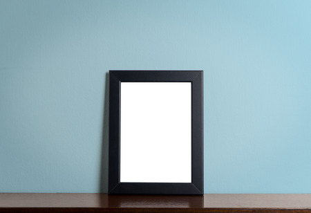 home accent: Black modern picture frame on Blue background. Black photo frame made of paper on a Blue cement background. Stock Photo