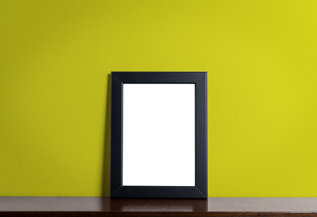 room accent: Black modern picture frame on Yellow background. Black photo frame made of paper on a Yellow cement background. Stock Photo