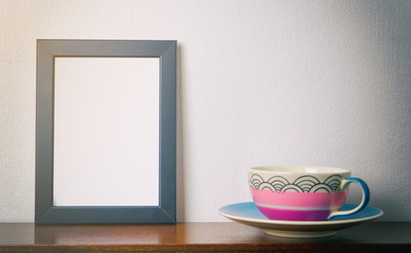 room accents: Blank photo frame with tea cup in vintage tone. Stock Photo