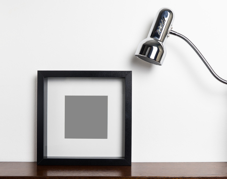 home accent: Thick black photo frame with light lamp on shelf