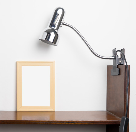 room accent: Wooden photo frame on white background with light lamp on top. Blank Picture frame for your picture or text. Stock Photo