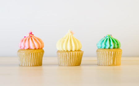 aligning: Three pastel color cup cake aligning on white table. Stock Photo