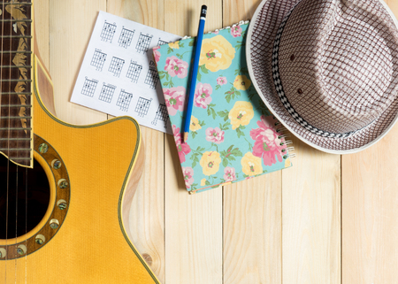 writing western: Guitar Music and summer hat Music writing on wooden background.