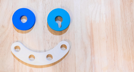 wooden toy: Children wooden toy smiling robot on wooden background.