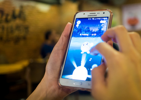 gameplay: Bangkok, Thailand - August 6, 2016: A girl is playing Pokemon Go on her samsung mobile in a restaurant.